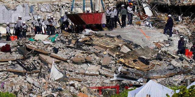 Workers search the rubble at the Champlain Towers South Condo on Monday. (AP)