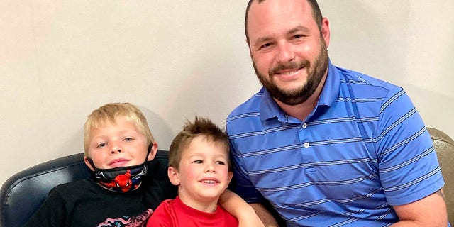 June 7, 2021: From left, 7-year-old Russell Bright, 5-year-old Tucker Bright, and dad Adam Bright pose for a picture at Ochsner Medical Center in Jefferson, La.