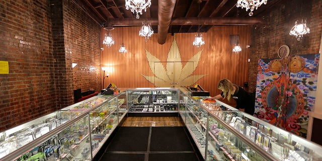Dec. 7, 2015: In this photo, a worker cleans a display case at the Ganja Goddess Cannabis Store in Seattle.