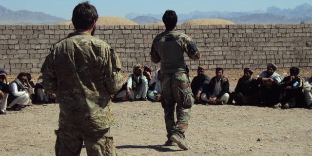 Moneer and Greg Adams speaking to village elders and recruits from throughout the Afghan district.