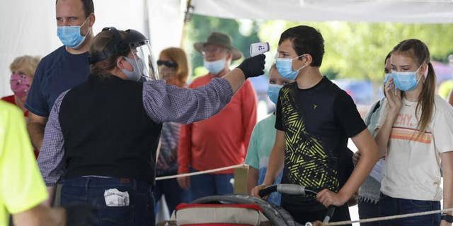 On June 13, 2021, a Silver Dollar City employee takes the temperature of guests before they are allowed to enter the park just west of Branson, Mo. (Nathan Papes/The Springfield News-Leader via AP, File)