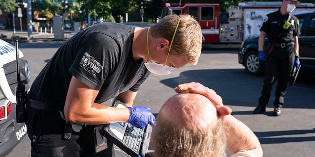 A paramedic with Falck Northwest ambulances treats a man experiencing heat exposure during a heat wave, 星期六, 六月 26, 2021, in Salem, 矿石. (AP Photo/Nathan Howard)