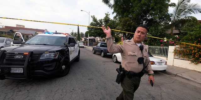 A Los Angeles County Sheriff's official works on the scene after three young children were found dead in a bedroom at a residence in East Los Angeles, Monday, June 28, 2021. (AP Photo/Ringo H.W. Chiu)