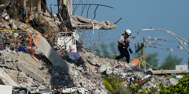 A man descends from the rubble pile, as members of the search and rescue personnel work atop the debris at the Champlain Towers South condo building on Friday. (AP)