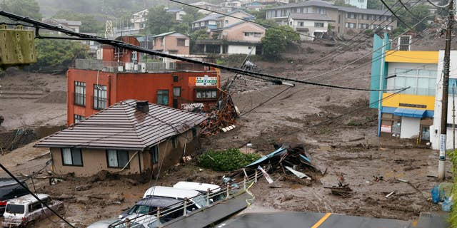 This photo shows buildings damaged by a mudslide on Saturday, July 3, 2021, in the Izusan neighborhood of Atami, west of Tokyo, following heavy rainfall in the area.  The mudslide, with a flood of black water and debris, crashed into rows of houses in the city after heavy rainfall on Saturday, leaving several people missing, officials said.  (Kyodo news via AP)