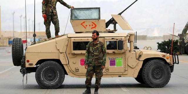 Afghan army soldiers stand guard after the American military left Bagram air base, in Parwan province north of Kabul, Afghanistan, Monday, July 5, 2021.