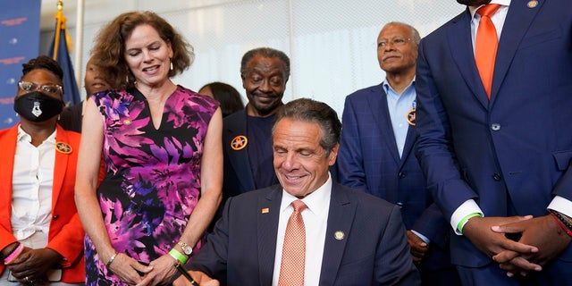 Surrounded by supporters and advocates, New York Governor Andrew Cuomo, center, signs legislation on gun control in New York, Tuesday, July 6, 2021. Cuomo signed two pieces of legislation to combat gun violence in New York state.