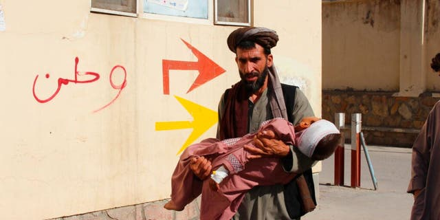 An Afghan civilian carries a wounded child to hospital after being injured in fighting between the Taliban and the government in Badghis province, northwestern Afghanistan on Wednesday July 7, 2021.