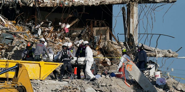 Search and rescue personnel remove remains on a stretcher as they work atop the rubble at the Champlain Towers South condo building where scores of people remain missing more than a week after it partially collapsed, Friday, July 2, 2021.