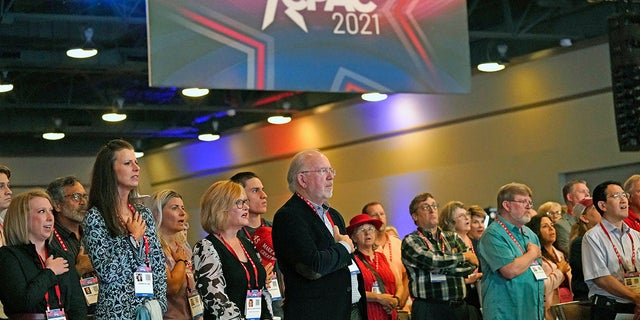 Conservative supporters place their hands over their chest during the national anthem at the opening general session of the Conservative Political Action Conference (CPAC) Friday, July 9, 2021, in Dallas. (AP Photo/LM Otero)