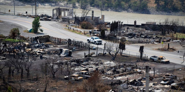 A Royal Canadian Mounted Police (RCMP) vehicle drives past the remains of vehicles and structures in Lytton, British Columbia, Friday, July 9, 2021, after a wildfire destroyed most of the village on June 30. (Darryl Dyck/The Canadian Press via AP)