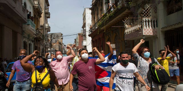 Government supporters shout slogans as anti-government protesters march in Havana, Cuba, Sunday, July 11, 2021.
