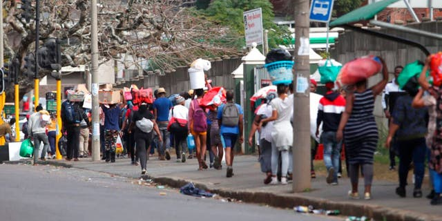 People make their way from a shopping mall carrying goods in Durban, South Africa, Tuesday July 13, 2021, as the looting and violence continue.