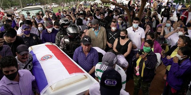 Pallbearers carry the coffin that contain the remains of Leidy Vanessa Luna Villalba outside her home, in Eugenio Garay, Paraguay, Tuesday, July 13, 2021. Luna Villalba, a nanny employed by the sister of Paraguay's first lady Silvana Lopez Moreira, was among those who died in the Champlain Towers South condominium collapse in Surfside, Florida on June 24. (AP Photo/Jorge Saenz)