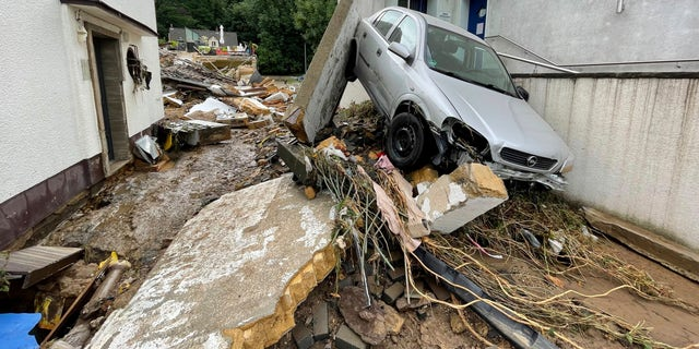 Puin bedekte een straat in de Duitse stad Bad Muenstrifel, donderdag 15 juli 2021, na hevige regenval en de overstroming van de rivier de Erft.  Mensen zijn omgekomen en tientallen worden vermist in Duitsland nadat hevige overstromingen beken en straten in razende stromen hebben veranderd, auto's hebben overspoeld en sommige gebouwen hebben doen instorten.  (B&S/dpa via AP)