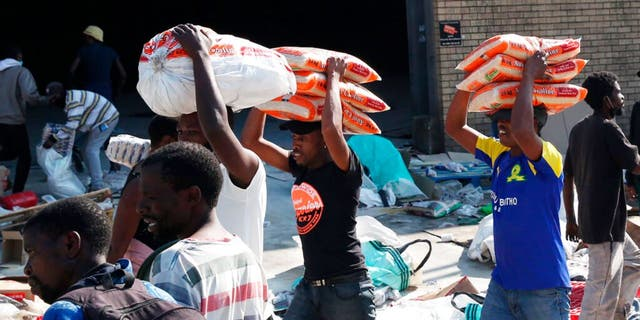 People carry bags of rice from a factory in Mobeni, south of Durban South Africa, Thursday, July 15, 2021, as unrest continues in the KwaZulu Natal province.
