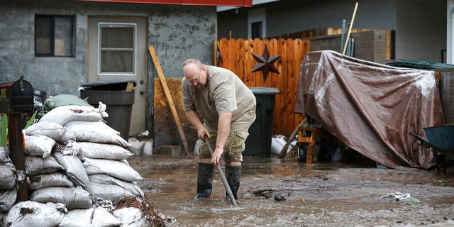 A resident shovels back floodwater as monsoon rains fell on the Museum Fire burn area causing flooding from the Paradise Wash in east Flagstaff, Ariz. on Wednesday, July 14, 2021. The threat of flash flooding will remain through next week, the National Weather Service said, though the coverage will be more scattered than widespread. (Jake Bacon/Arizona Daily Sun via AP)