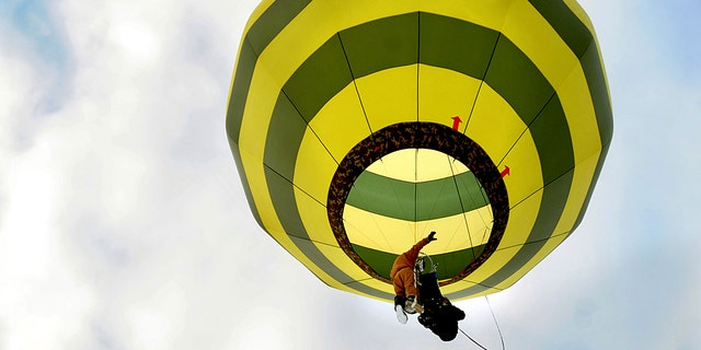 In a harness he created, Brian Boland, of Post Mills, Vermont, takes off attached to a hot-air balloon with a passenger above Westshire Elementary School in West Fairlee, Vt., on Feb. 26, 2013. (Associated Press)