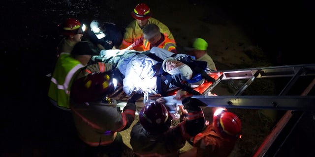 In this photo provided by the Iron County Sheriff's Department, emergency personnel remove an injured train worker from the scene of a derailment near Lund, Utah, on Thursday, July 15, 2021. Three workers on a freight train were injured when it derailed while crossing tracks covered with water in a remote part of southern Utah Thursday night, authorities said. The train, which had nearly 100 cars, tipped on its side after derailing near Lund, about 85 miles from the Nevada border. (Iron County Sheriff's Dept. via AP)