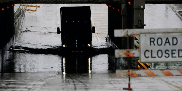 A semi-trailer drives through a flooded street, Friday, July 16, 2021, in Dearborn, Mich. Detroit area residents are still drying out their basements from the flooding last month, but now more flooding is on the horizon as a heavy rain front moves through southern Michigan. (AP Photo/Carlos Osorio)