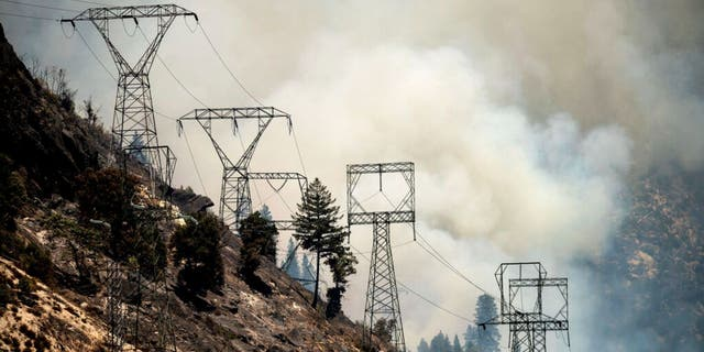 Smoke billows behind power lines as the Dixie Fire burns along Highway 70 in Plumas National Forest, Calif., on Friday, July 16, 2021.