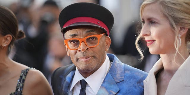 """Jury president Spike Lee (middle) posed for photographers upon arrival at the awards ceremony and premiere of the closing film """"OSS 117: From Africa with Love"""" at the 74th International Film Festival in Cannes, southern France, Saturday, July 17, 2021. (AP Photo/Vadim Ghirda)"""