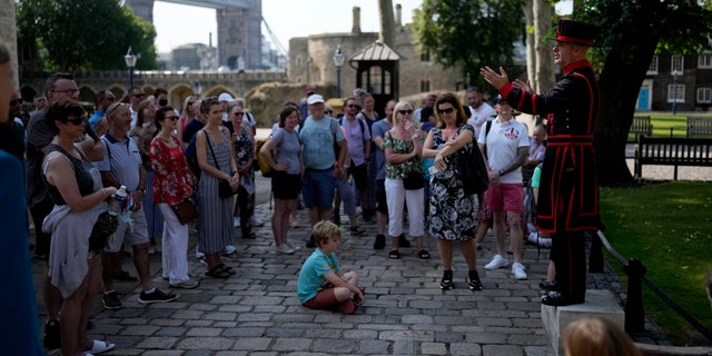 """On what some have called """"Freedom Day"""", marking the end of coronavirus restrictions in England, visitors listen as Yeoman Warder Barney Chandler leading the first tour of the Tower of London in 16 months since the start of the coronavirus outbreak, in London, Monday, July 19, 2021. Beginning Monday, face masks will no longer be legally required and with social distancing rules shelved, but mask rules will remain for passengers on the London transport network. (AP Photo/Matt Dunham)"""
