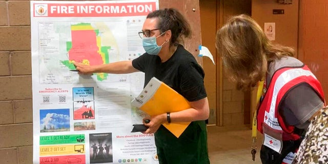 In this photo provided by the Bootleg Fire Incident Command, a public information officer talks with evacuees at a Red Cross Shelter near the Bootleg Fire in southern Oregon, Sunday, July 18, 2021. (Bootleg Fire Incident Command via AP)