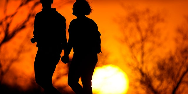 A couple walks through a park at sunset in Kansas City, Mo on March 10, 2021. (AP Photo/Charlie Riedel, File)