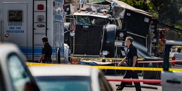 In this July 1, 2021 file photo, police officers walk past the remains of a Los Angeles Police Department armored tractor-trailer after illegal fireworks were seized at a South Los Angeles home.  (AP Photo/Damian Dovarganes, File)