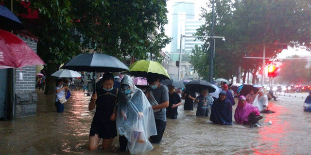 People move through flood water after a heavy downpour in Zhengzhou city, central China's Henan province on Tuesday, July 20, 2021. Heavy flooding has hit central China following unusually heavy rains, with the subway system in the city of Zhengzhou inundated with rushing water thousands of residents having to be relocated. (Chinatopix Via AP)