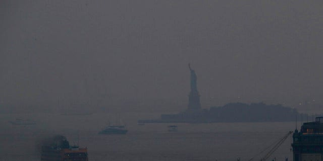The Staten Island Ferry departs from the Manhattan terminal through a haze of smoke with the Statue of Liberty barely visible, Tuesday, July 20, 2021, in New York.