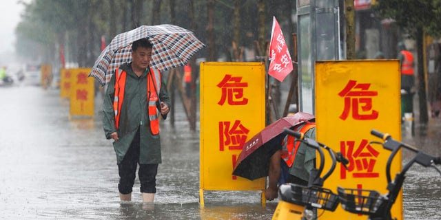 """In this photo released by Xinhua News Agency, staff members set up warning signs with the words """"Danger!"""" at a waterlogged area in Wuzhi County in central China's Henan Province on Tuesday, July 20, 2021. At least a dozen people died in severe flooding Tuesday in a Chinese provincial capital that trapped people in subways schools, washed away vehicles stranded people in their workplaces overnight. (Feng Xiaomin/Xinhua via AP)"""