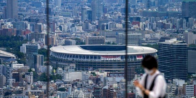 یک مرد در حال گرفتن عکس از یک عرشه رصد است ، زیرا استادیوم ملی ، جایی که مراسم افتتاحیه بازی های المپیک توکیو در آن برگزار می شود ، در پس زمینه توکیو دیده می شود.