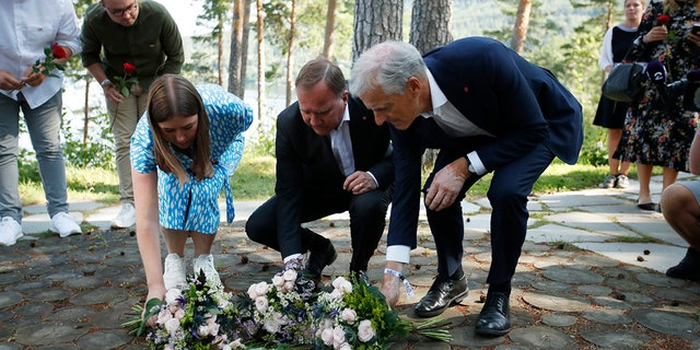 Leader of AUF youth political league in Norway, Astrid Hoem, Prime Minister of Sweden Stefan Lofven and leader of the Norwegian Labor Party Jonas Gahr Store, lay flower tributes at the memorial on Utoya island Wednesday, July 21, 2021. (Beate Oma Dahle / NTB via AP)