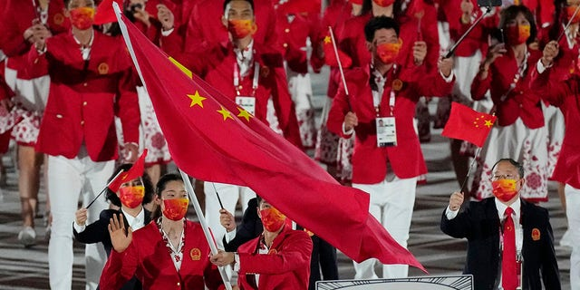 Zhu Ting and Zhao Shuai, of China, carry their country's flag during the opening ceremony in the Olympic Stadium at the 2020 Summer Olympics, Friday, July 23, 2021, in Tokyo, Japan. (AP Photo/David J. Phillip)