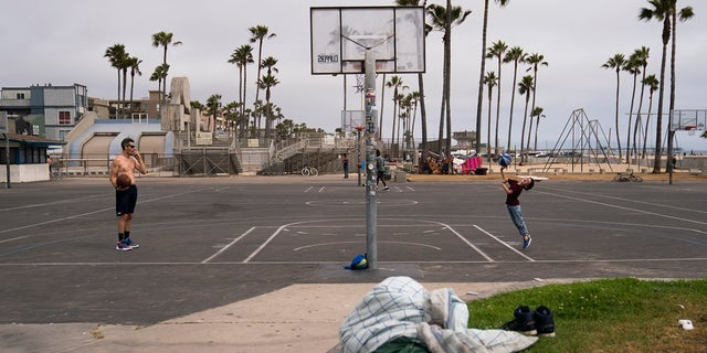 People play basketball as a homeless man sleeps near the court in the Venice neighborhood of Los Angeles, Tuesday, June 29, 2021.