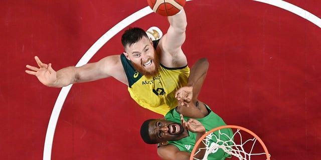 Australia's Aron Baynes, top, shoots over Nigeria's Ekpe Udoh during a men's basketball preliminary round game at the 2020 Summer Olympics, Sunday, July 25, 2021, in Saitama, Japan. (Aris Messinis/Pool Photo via AP)
