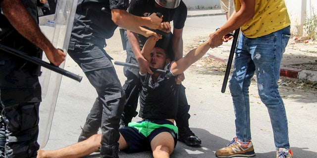 Tunisian police officers detain a protester during a demonstration in Tunis on Sunday. (AP)