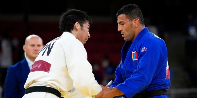 Takanori Nagase of Japan, at left shakes hand with Saeid Mollaei of Mongolia after defeating him to win the men -81kg final of the judo match at the 2020 Summer Olympics in Tokyo, Japan, Tuesday, July 27, 2021. (AP Photo/Vincent Thian)
