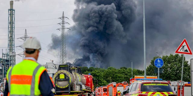 Emergency vehicles of the fire brigade, rescue services and police stand not far from an access road to the Chempark over which a dark cloud of smoke is rising in Leverkusen, Germany, Tuesday, July 27, 2021.