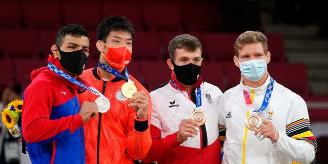 From left, silver medalist Saeid Mollaei of Mongolia, gold medalist Takanori Nagase of Japan, bronze medalists Shamil Borchashvili of Austria and Matthias Casse of Belgium celebrate during the award ceremony for the men -81kg judo match at the Olympics in Tokyo, Japan, Tuesday. (AP Photo/Vincent Thian)