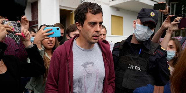 Roman Dobrokhotov, chief editor of The Insider, walks surrounded police officers and journalists, in Moscow, Russia, Wednesday, July 28, 2021.