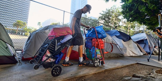 In this July 1, 2019 file photo, a homeless man moves his belongings from a street near Los Angeles City Hall, background, as crews prepared to clean the area. The Los Angeles City Council has passed a sweeping anti-camping measure to remove widespread homeless encampments that have become an eyesore across the city. (AP Photo/Richard Vogel, File)