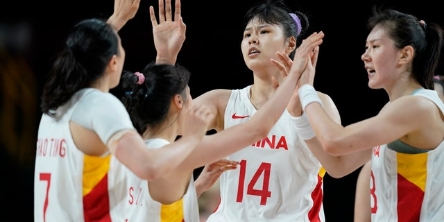 China's Yueru Li (14) celebrates with teammates against Australia during a women's basketball preliminary round game at the 2020 Summer Olympics in Saitama, Japan, Friday, July 30, 2021. (AP Photo/Charlie Neibergall)