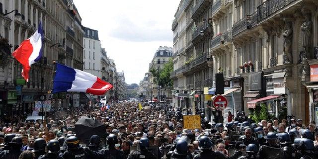 Những người biểu tình tuần hành vẫy cờ Pháp trong cuộc biểu tình ở Paris, Pháp, Thứ Bảy, ngày 31 tháng 7 năm 2021. Những người biểu tình đã tập trung tại một số thành phố ở Pháp vào Thứ Bảy để phản đối việc thông qua COVID-19, cho phép những người được tiêm chủng dễ dàng tiếp cận các địa điểm hơn.