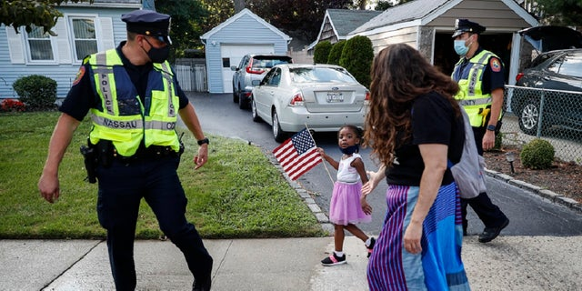 FILE - This photo from Monday July 13, 2020, shows Nassau County Police officers walk alongside protesters participating in a Black Lives Matter march through a residential neighborhood calling for racial justice in Valley Stream, N.Y.