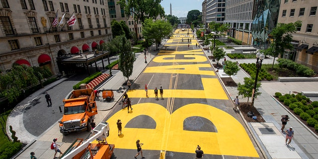 """People walk down 16th Street after volunteers paint with permission from the city """"Black lives count"""" on the street near the White House on June 05, 2020 in Washington, DC."""