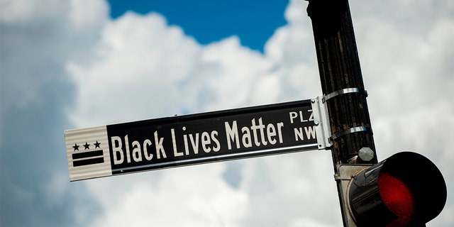 """A new street sign that reads """"Black Lives Matter Plaza NW"""" can be seen at the intersection of H and 16th Street near the White House in Washington DC, on June 5, 2020."""