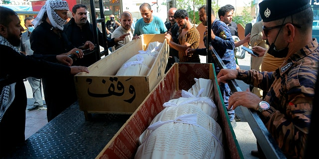 Mourners prepare to bury hospital fire victims in Najaf, Iraq, Tuesday, July 13, 2021.